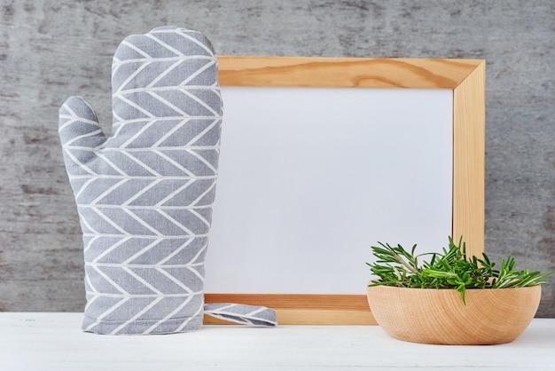 空のホワイトペーパー、鍋つかみ、白いテーブルにローズマリーボウルとキッチン用品の背景
