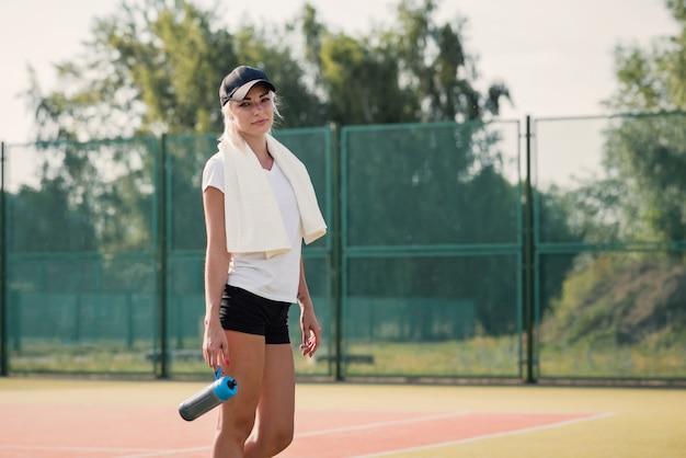 テニスコートでスポーツをした後休んで若い女性