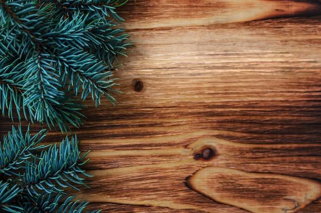 木製の背景上にクリスマスツリーの小枝