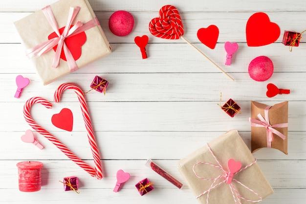 バレンタイン・デー。赤いハートのフレーム、白のリボンとお菓子のギフトボックス