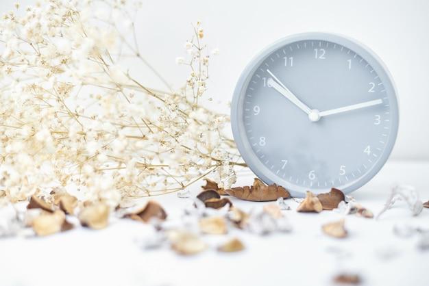 古典的な目覚まし時計、花の枝、白いテーブルの上の花びら