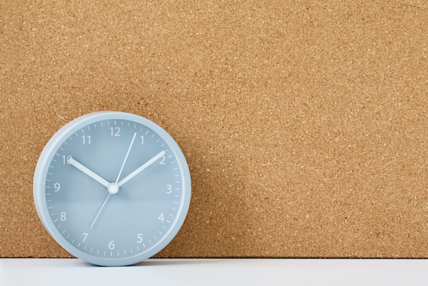 白いテーブルの上の灰色の目覚まし時計とコルクボード