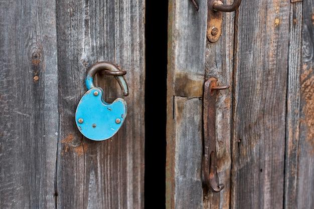 木製のドアに青い古いさびたロック解除南京錠