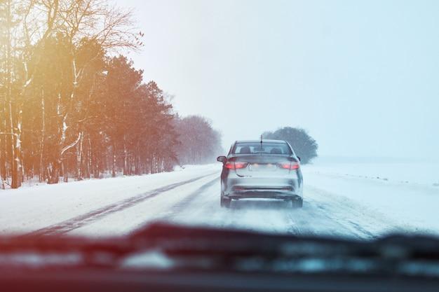 雪に覆われた冬の道で車の背面図