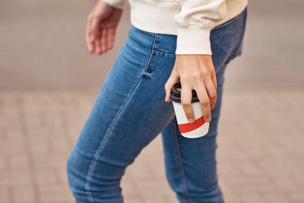 Женщина руку с бумажный стаканчик кофе забрать на улице города