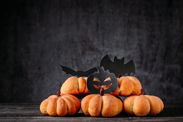 かぼちゃの形をした自家製ケーキと暗闇のハロウィーンの飾り。ハロウィーンの料理