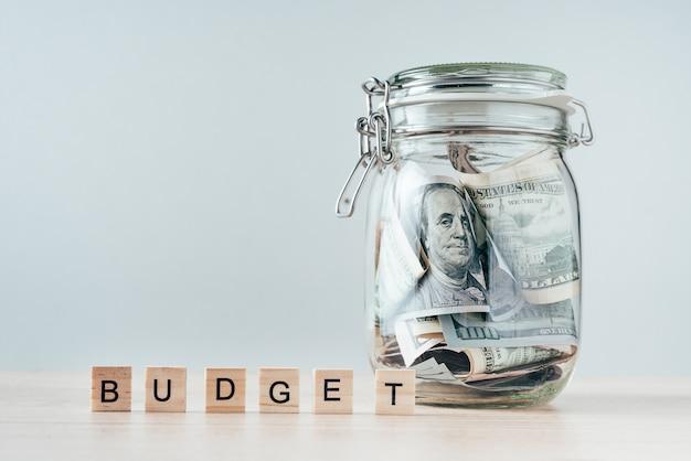 Слово бюджет и долларовые купюры в стеклянной банке
