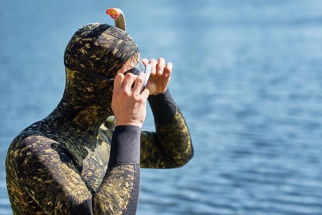 マスクとシュノーケルでウェットスーツを着たダイバーのクローズアップは、水に飛び込む準備をします