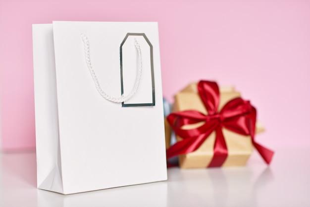Подарочная коробка с лентой и бумажной сумкой на розовом