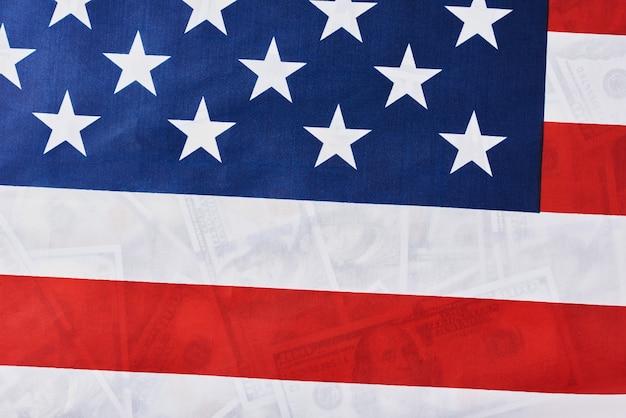 多くの米ドル紙幣の上にアメリカ国旗のクローズアップ。財務