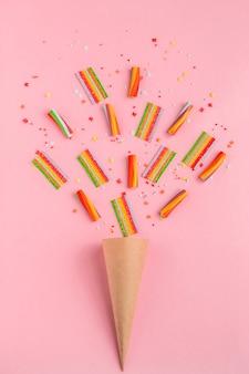 ピンクの背景にカラフルなマーマレードお菓子と紙の角