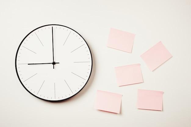 Настенные часы и розовые наклейки на белом фоне.