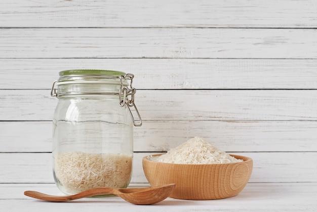 木製のボウルとガラスの瓶に米粒