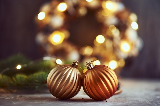 ゴールデンボール、モミの木の枝、暗い背景にガーランドライトのクリスマスの装飾