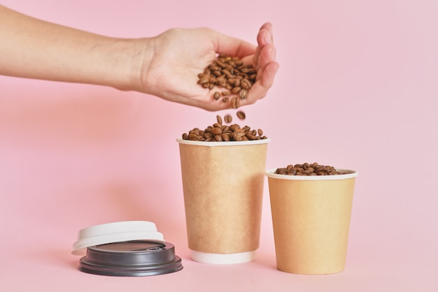 Женская рука окропляет кофейные зерна в бумажном стаканчике кофе на розовом фоне