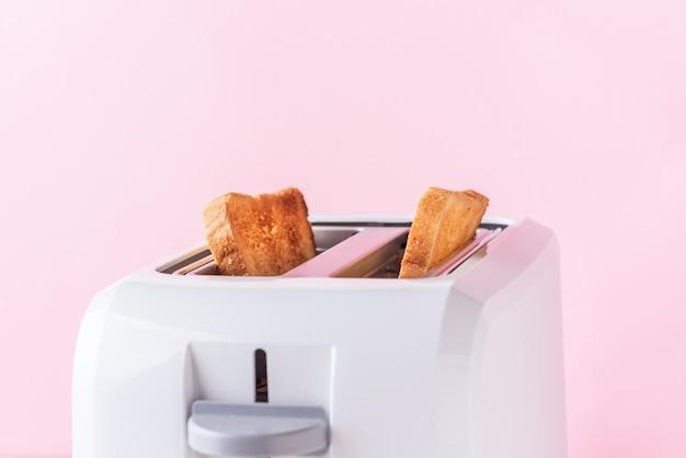ピンクの背景に焼きたてのパンと白いトースター