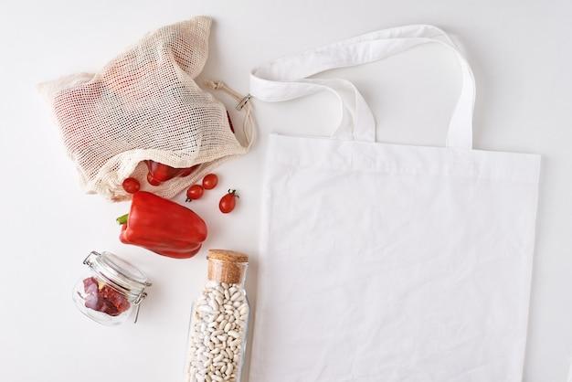 Стеклянная банка и хозяйственная сумка со свежими овощами