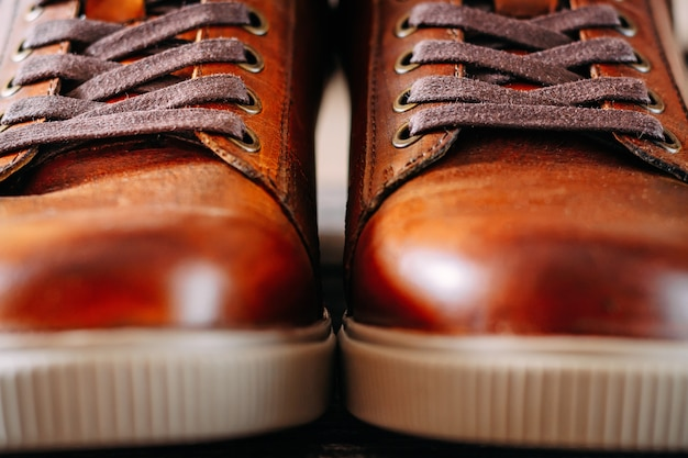 靴ひもを持つ男茶色の茶色の靴をクローズアップ