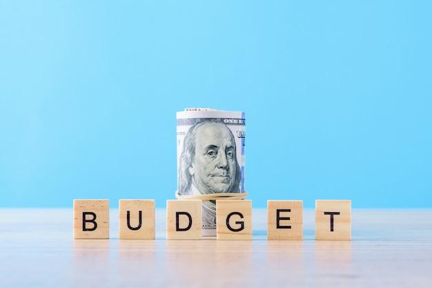 Свернутые долларовые банкноты и слово бюджет. концепция финансового учета