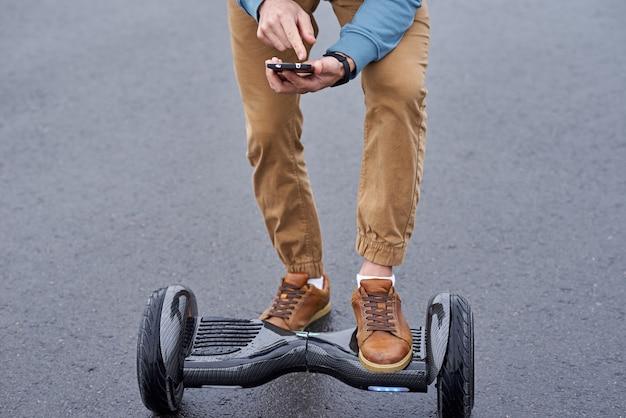 電気ジャイロスクーターのアプリケーションを持つ手にスマートフォン。男は屋外でホバーボードを使用します