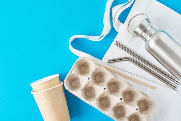 廃棄物ゼロのコンセプト。自然なショッピングバッグのエコフレンドリーな再利用可能なアイテム。ペーパーエッグトレイ、コーヒーカップ、アルミボトル、金属チューブ