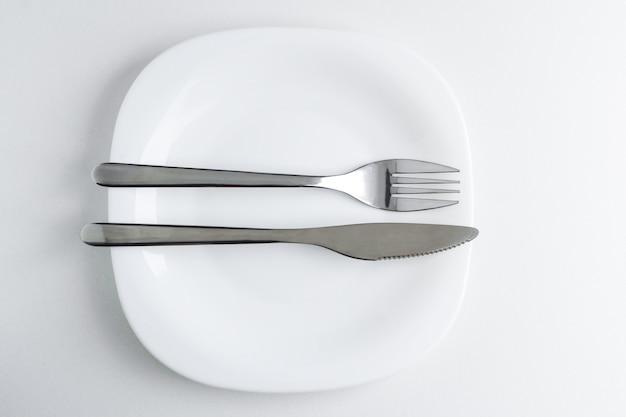 フォークとナイフは白い皿の上にあります。
