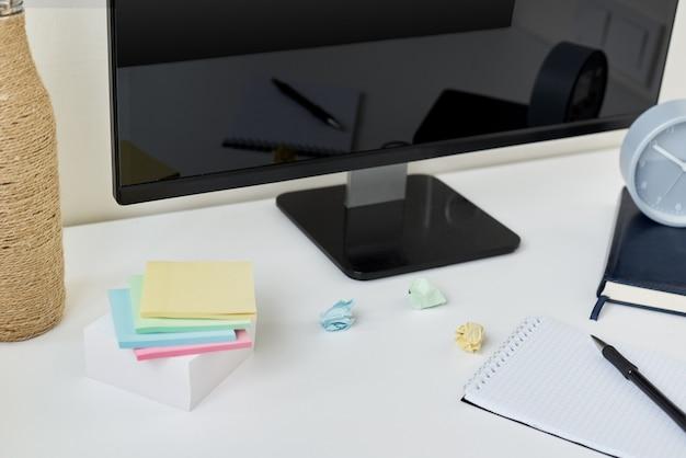 デスクトップ、時計、事務用品、付箋があるモダンなワークスペースまたは職場