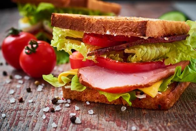 Домашний бутерброд с ветчиной, листьями салата, сыром и помидорами на деревянном фоне