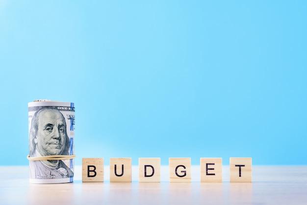 Свернутые вверх долларовые банкноты и бюджет слова на синем фоне. концепция финансового учета