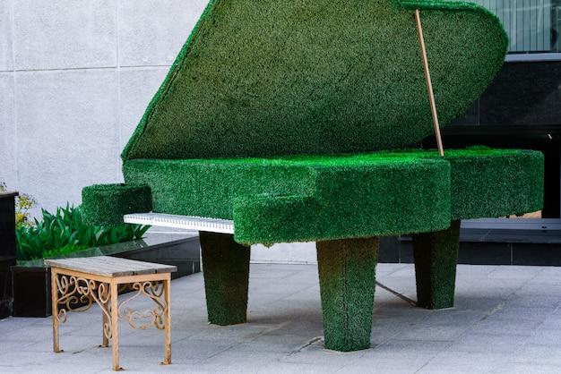 Пианино из зеленых растений в городском пейзаже