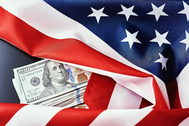 暗い背景にアメリカ国旗とドル札。ファイナンスの概念