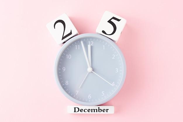 ピンクの背景の目覚まし時計でクリスマスの背景