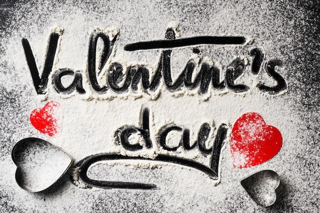 小麦粉と暗い背景に赤い紙のハートからの装飾で書かれた言葉バレンタインデー。バレンタインデーのコンセプト