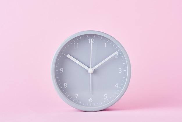 パステルピンクの背景に灰色の古典的な目覚まし時計をクローズアップ