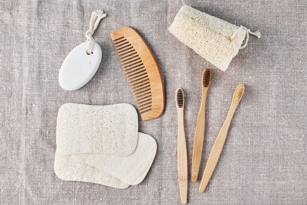 リネンの背景に竹の歯ブラシ、ヘチマのスポンジ、木製のヘアブラシを入浴するための自然なセット。廃棄物ゼロのプラスチックコンセプト