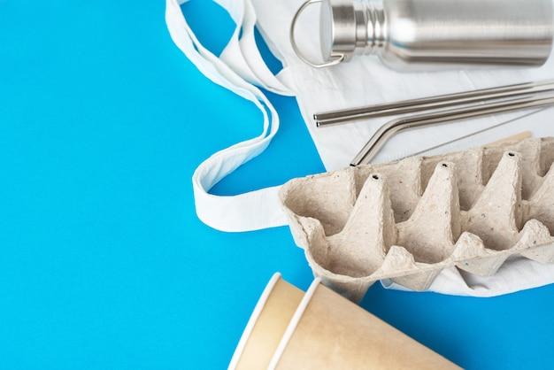廃棄物ゼロのコンセプト。エコショッピングバッグのエコフレンドリーな再利用可能なアイテム。紙の卵トレイ、コーヒーカップ、アルミボトル、青色の背景に金属管