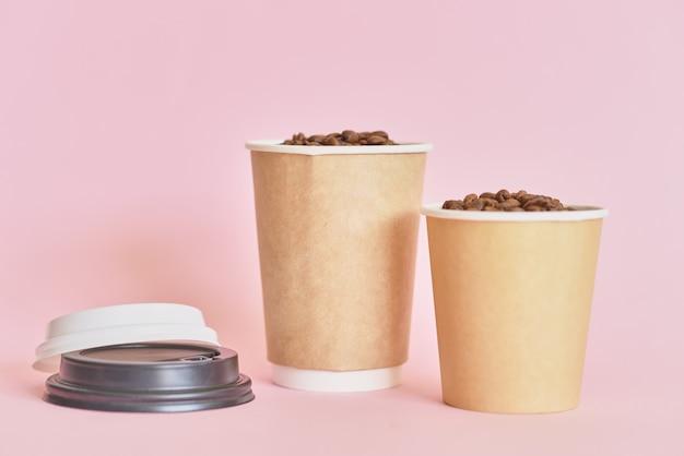 Две бумажные кофейные чашки с кофейными зернами на розовом фоне