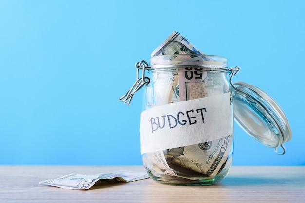 Концепция богатства. стеклянная банка с долларовыми банкнотами и надписью бюджета на синем фоне