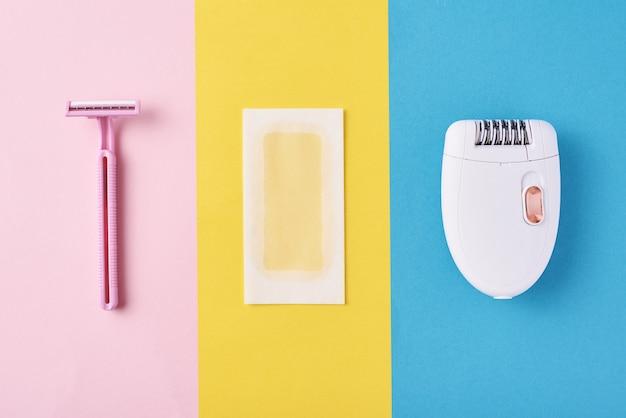 Эпилятор, бритва и восковые полоски на цветном фоне