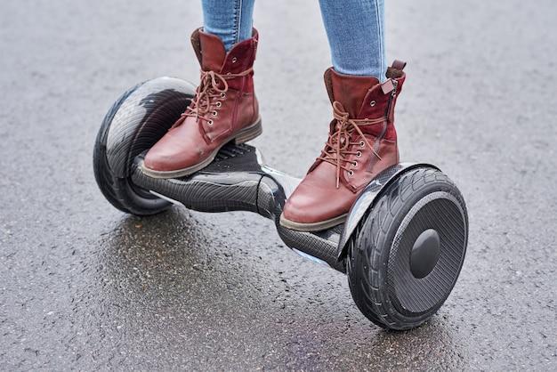 アスファルトの道路でホバーボードを使用して女性のクローズアップ。電動スクーター屋外の足