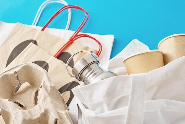 廃棄物ゼロのコンセプト。自然な買い物袋に入った環境に優しい再利用可能なアイテム。紙袋、コーヒーカップ、金属ボトル