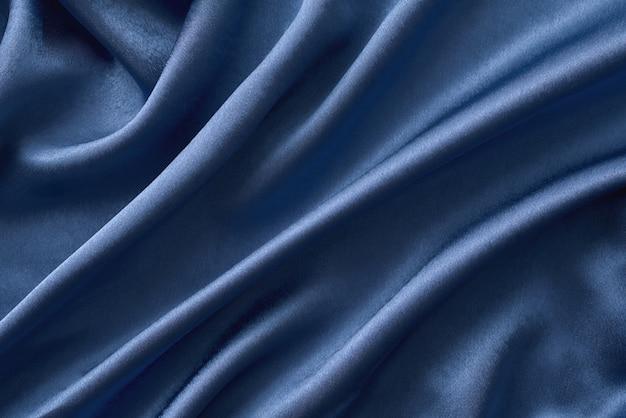 ひだにシルバーシルクの背景。波状のシルク表面の抽象的なテクスチャ