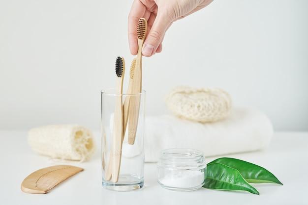女性の手は、バスルームのインテリアに木製の竹歯ブラシを取ります。プラスチックゼロ廃棄物の概念はありません。ガラス、タオル、歯磨き粉、白い背景の手ぬぐいでエコフレンドリーな歯ブラシ