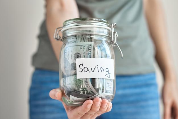 ドル紙幣でいっぱいの碑文とガラスの瓶を保持している女性の手。お金と家の予算の概念を保存