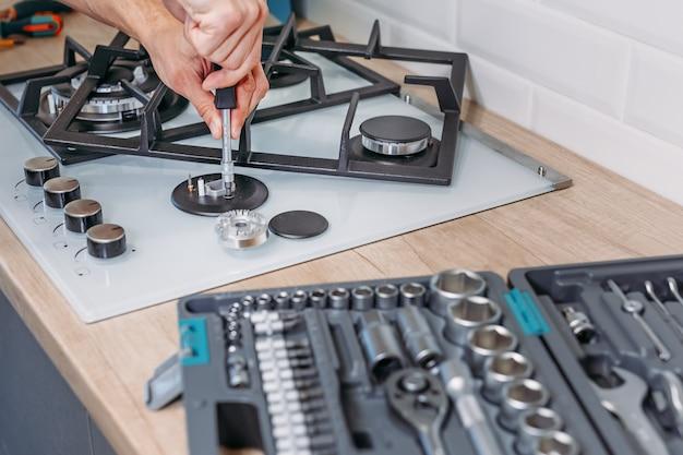 Мужская рука ремонтирует конфорку газовой панели с помощью отвертки