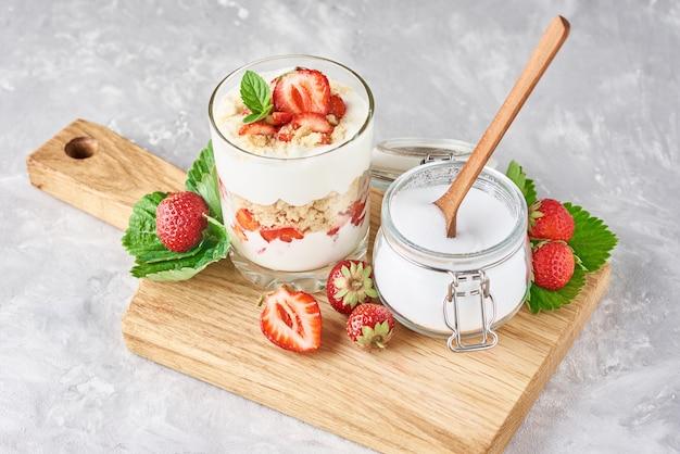 ガラス、新鮮な果実、まな板、トップビューで砂糖を瓶にイチゴとグラノーラやヨーグルト
