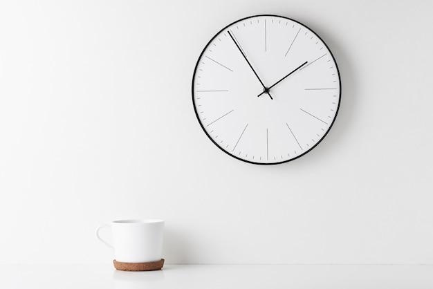 壁掛け時計を備えたホームオフィスの最小限のワークスペースデスク