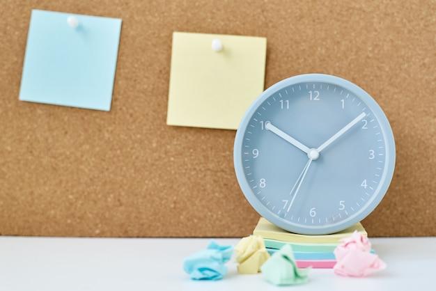 メモ、目標、メモ、またはアクションプランの概念。職場のオフィスや自宅のコルクボードと目覚まし時計の付箋