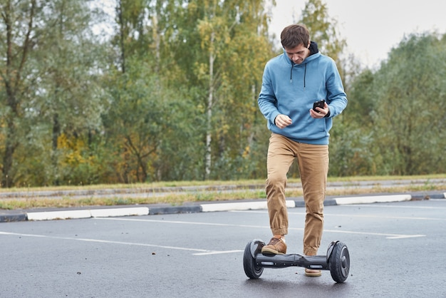 Человек верхом на ховерборде и с помощью смартфона на открытом воздухе