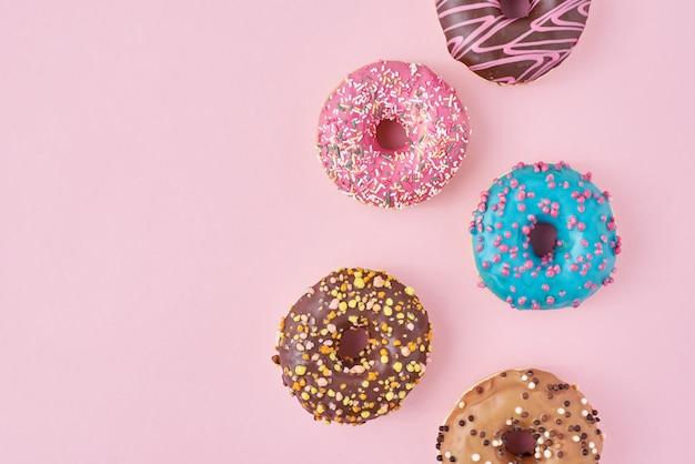 さまざまな種類のカラフルなドーナツと装飾された振りかけるとパステルピンクの背景にアイシング、平面図フラットレイアウト